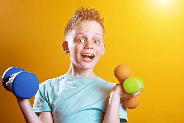 Un niño en una camiseta brillante con pesas en un amarillo