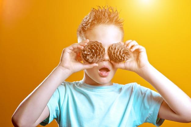 Un niño con una camiseta ligera le puso dos conos en los ojos