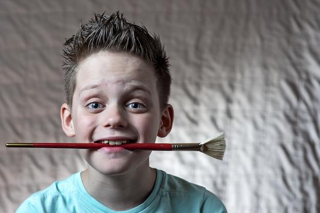 Niño en una camiseta ligera sosteniendo un pincel de arte en su boca y sonriendo