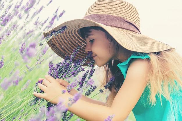 Un niño en un campo de flores de lavanda. enfoque selectivo