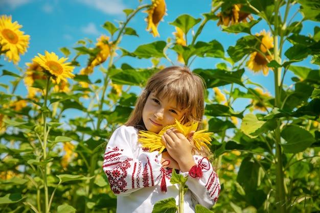 Un niño en un campo de girasoles con una camisa bordada.