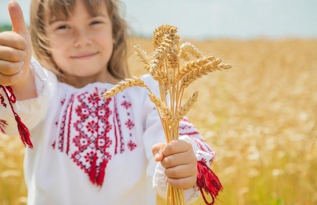 Un niño en un campo de trigo con una camisa bordada.