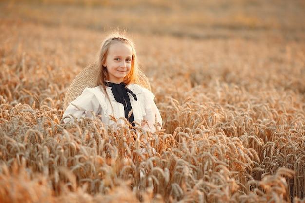 Niño en un campo de verano. niña con un lindo vestido blanco.