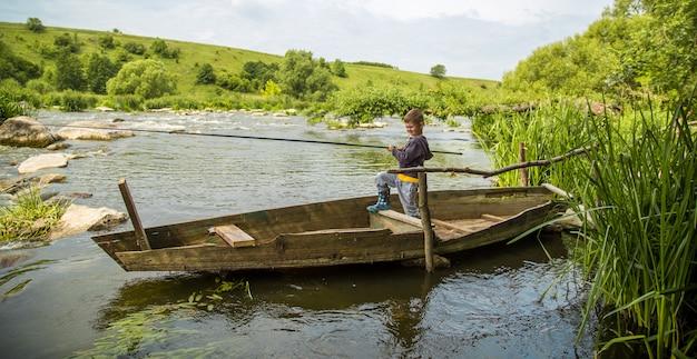 Niño con caña de pescar en un bote de madera