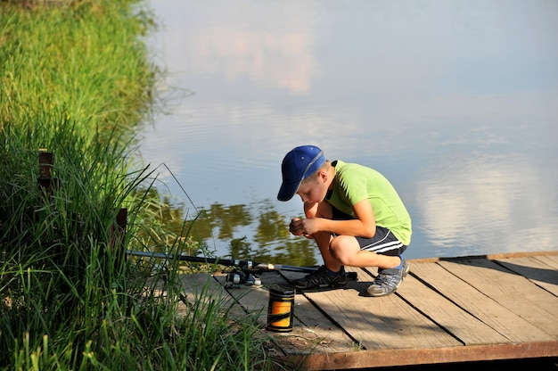 El niño con una caña de pescar. pesca en un lago en un verano soleado