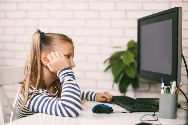 Un niño cansado se sienta en casa en un escritorio de computadora y hace la tarea.