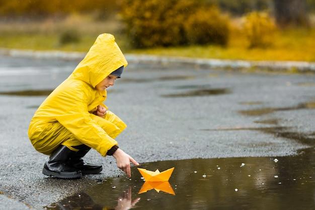 Niño con capa impermeable amarilla y botas de goma negras jugando con papel barco de juguete hecho a mano en un charco al aire libre bajo la lluvia en otoño.
