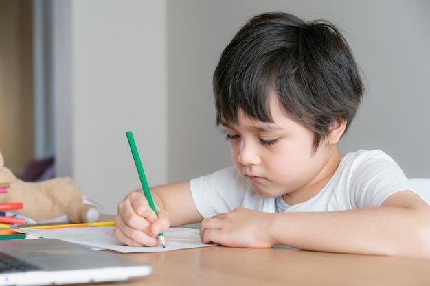 Niño con cara infeliz haciendo los deberes, niño aburrido con lápiz verde para colorear