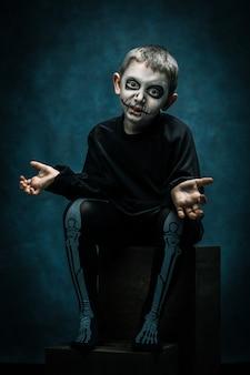 Niño con cara de maquillaje fantasma para fiesta de halloween. tiro del estudio