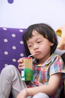 El niño de la cara soñolienta se sienta y se aburre de beber leche mientras sostiene la mano
