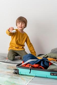 Niño en casa con figurilla de avión y equipaje.