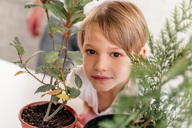 Niño en casa junto a plantas.