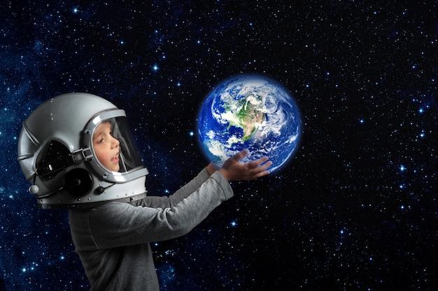 Un niño con casco de astronauta sostiene la tierra en sus manos