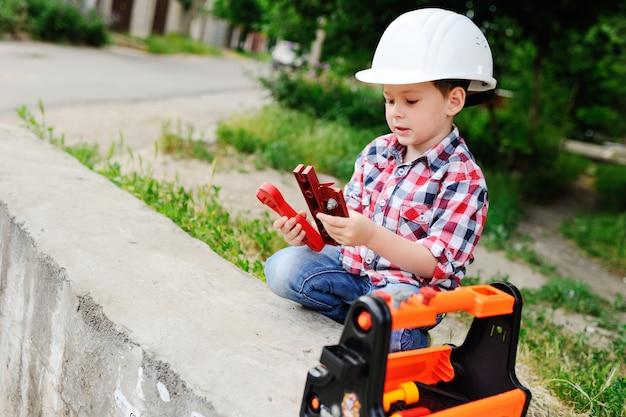Niño en casco de construcción blanco.