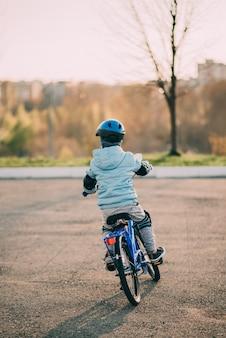 Niño en casco monta una bicicleta en un día soleado