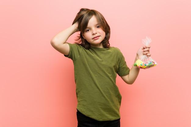 Niño caucásico con caramelos sorprendidos, ha recordado una reunión importante.