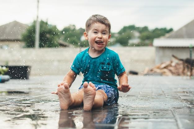 Niño caucásico emocional está jugando con agua en el suelo sonriendo a la cámara en el patio trasero