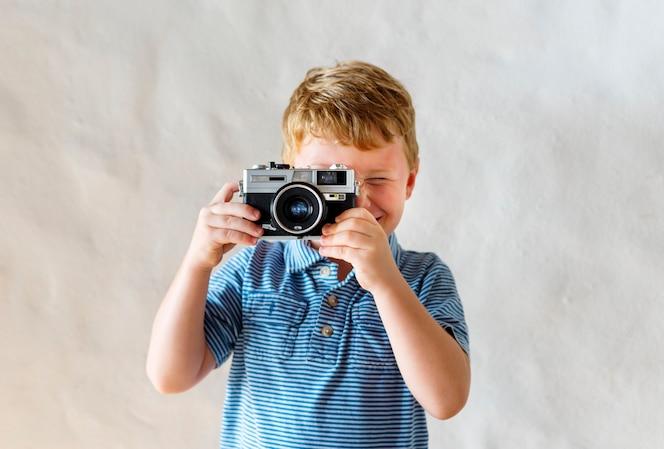 Niño caucásico jugando con una cámara