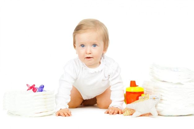 Niño caucásico con pañales apilados y juguetes aislados sobre fondo blanco.