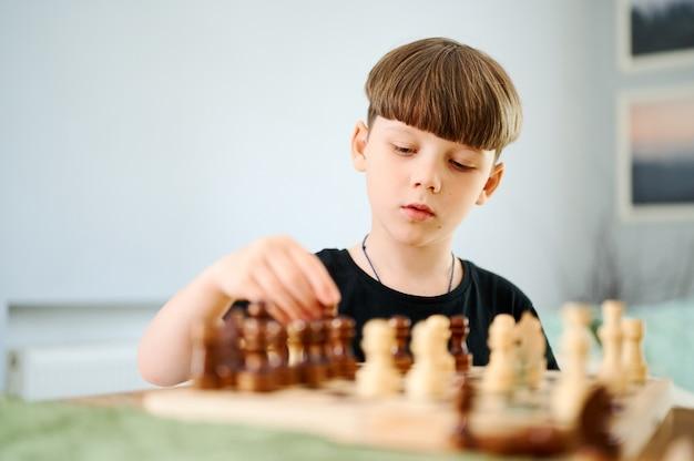 Niño caucásico preescolar inteligente jugando al ajedrez en casa