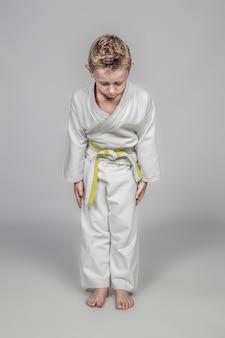 Niño caucásico de siete años practicando artes marciales. posición de rei.