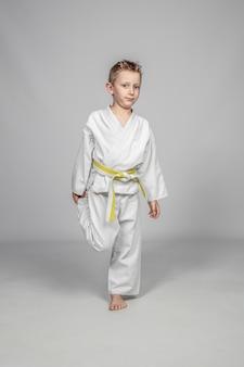 Niño caucásico de siete años practicando artes marciales.