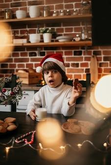 Un niño caucásico sorprendido está sentado en la mesa de la cocina con un suéter blanco y un sombrero rojo de navidad con leche y galletas