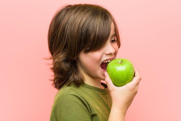 Niño caucásico sosteniendo una manzana