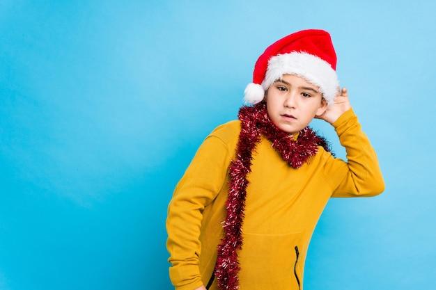 Niño celebrando el día de navidad con un sombrero de santa aislado tratando de escuchar un chisme.