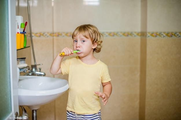 Niño cepillándose los dientes en el baño.