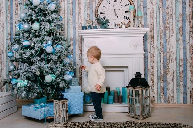 Niño cerca de la chimenea y el árbol de navidad