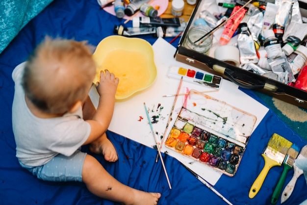 Niño cerca de pinceles, acuarelas y caja sentada en una colcha