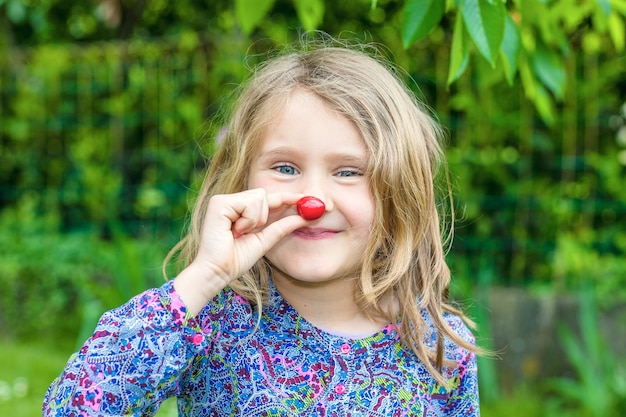 Niño con cereza en la mano en un jardín.