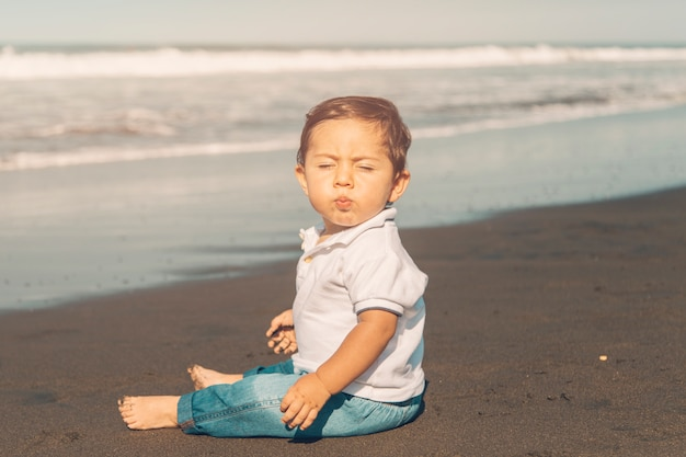 Niño cerrando los ojos mientras está sentado en la playa de arena