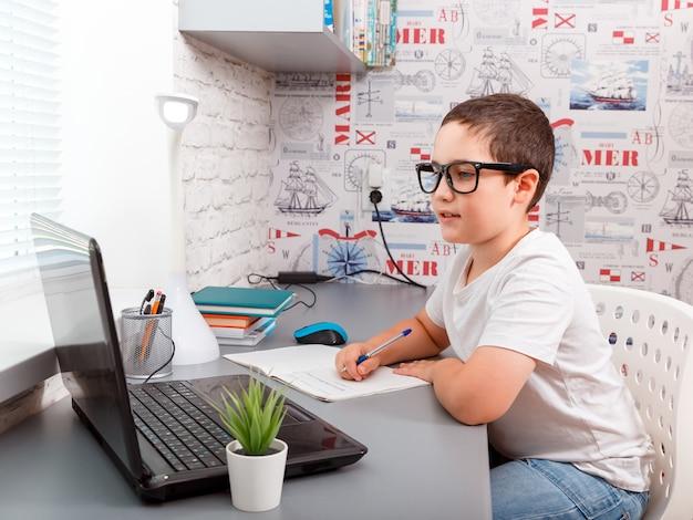 Niño chico haciendo los deberes en la computadora portátil en la plataforma en línea