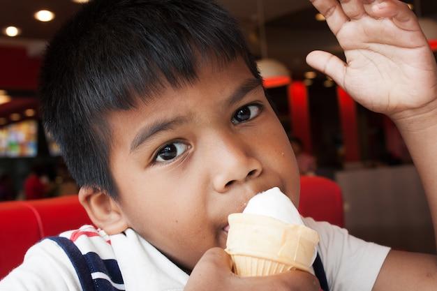 Niño chico mano sosteniendo un cono de helado de goteo
