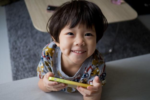 Un niño chino adicto al teléfono, una niña asiática que juega un teléfono inteligente, un niño usa el teléfono, mira un teléfono inteligente, mira dibujos animados