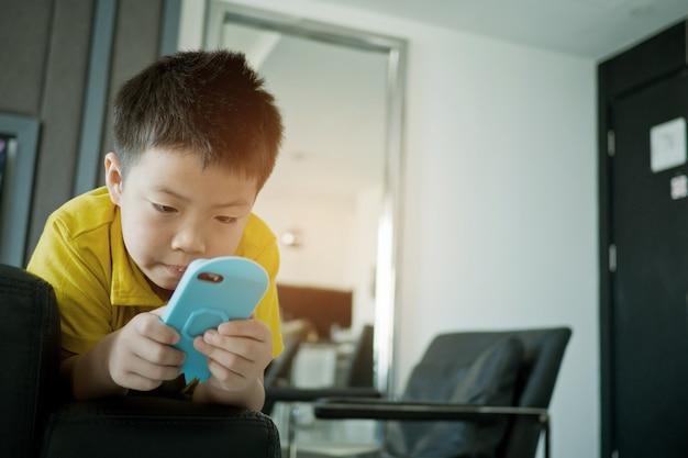 Niño chino asiático jugando teléfono inteligente en la cama, el niño usa el teléfono y juega, adictos y dibujos animados,