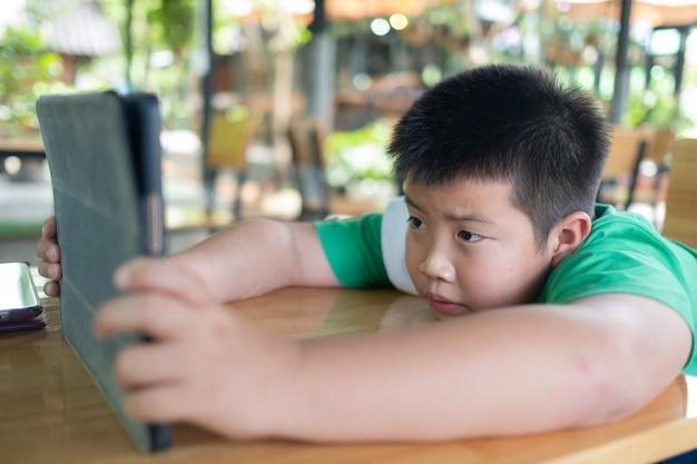 Niño chino asiático jugando teléfono inteligente, teléfono de uso infantil y juego, juego adicto y dibujos animados