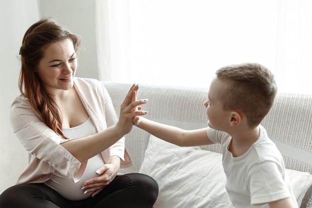 Niño choca los cinco con la mamá embarazada sentada en el sofá en casa.