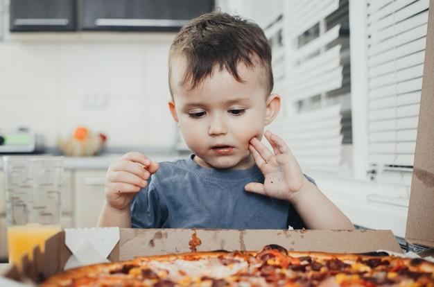 El niño en la cocina come una pizza enorme y bebe jugo, muy divertido