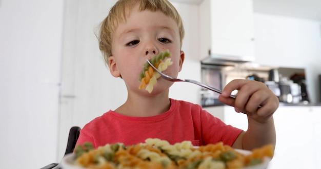 El niño en la cocina a la mesa comiendo macarrones.