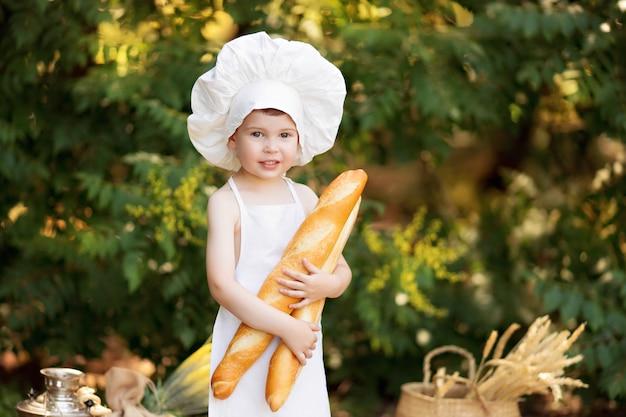 Niño cocina en la naturaleza en un día soleado de verano. el pequeño panadero come pan y panecillos en un delantal blanco