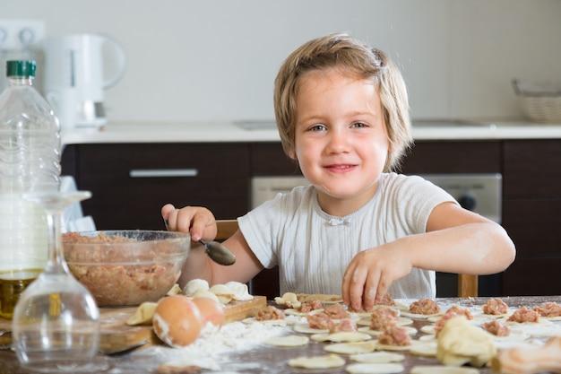 Niño cocinando albóndigas de carne