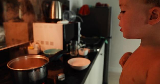 Niño cocinando sola en casa. el niño saca un tenedor caliente de la sartén y lo quema.