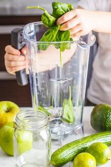 Niño cocinar espinaca manzana pepino batido. concepto de alimentos basados en plantas saludables.