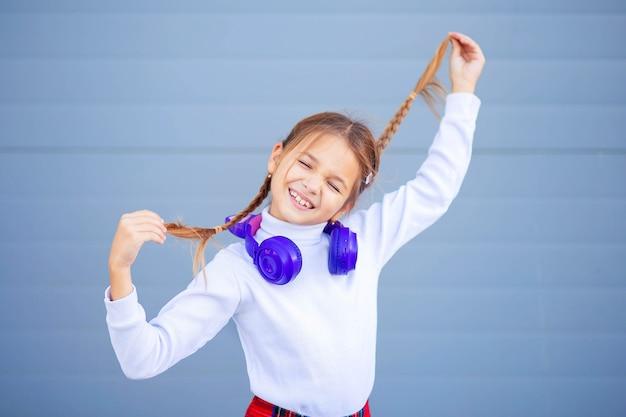 Un niño, un colegial, escucha música con auriculares inalámbricos brillantes y baila alegremente. auriculares bluetooth modernos con orejas para niñas.