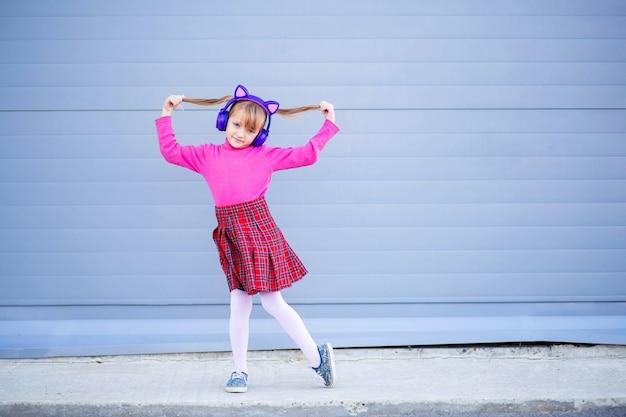 Un niño, un colegial, escucha música con auriculares inalámbricos brillantes y baila alegremente.