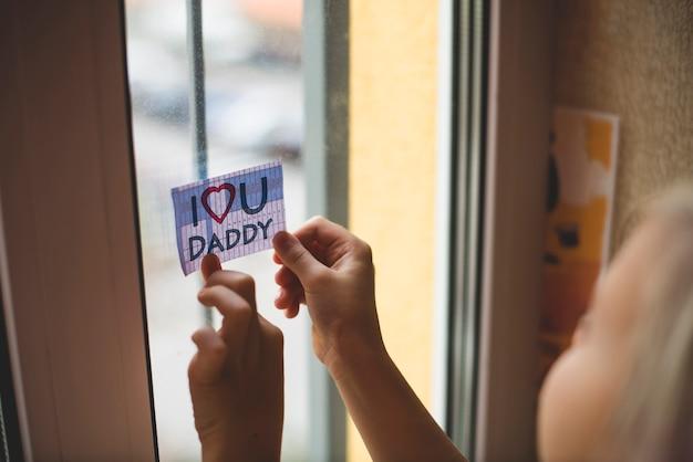 Niño colocando una nota en la ventana para su padre