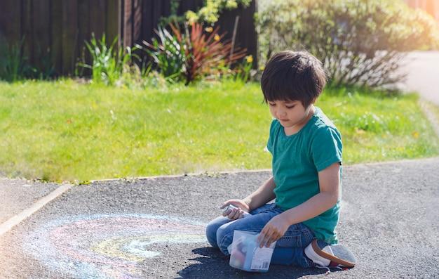 Niño para colorear arco iris con tizas de colores en el sendero